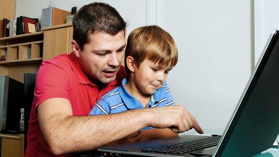 Vater und Sohn sitzen zusammen am Laptop. © Gina Sanders fotolia Foto: Gina Sanders