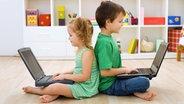 Zwei Kinder sitzen Rücken an Rücken auf dem Boden mit einem Laptop auf den Beinen. © Ilike fotolia Fotograf: Ilike
