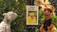 """Wolle und Finchen betrachten das Plakat """"Mama gesucht"""". © NDR Foto: screenshot"""