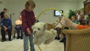 Lea lässt den Hund Kasper einen Sprung durch den Reifen machen. © NDR Fotograf: Melnanie Kuss