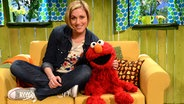 Julia Stinshoff sitzt mit Elmo auf einem Sofa im Spielehaus. © NDR Fotograf: Uwe Ernst