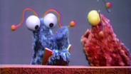 Die Yip Yips neben einer Standuhr. © NDR Sesame Workshop Foto: screenshot